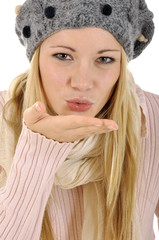 Junge Frau in Winterleidung gibt Luftkuss