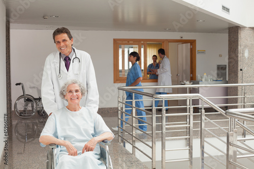 Laughing doctor pushing a wheelchair