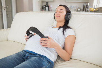 Pregnant woman holding headphones to belly and listening to musi
