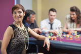 Smiling woman taking break from roulette with champagne