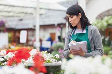 Worker taking notes while choosing a flower