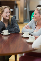Women sitting at the coffee shop laughing