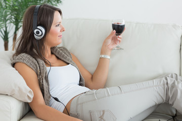Woman lying on the sofa and listening to music with a red wine g