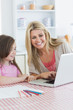 Mother and girl sitting at the kitchen with laptop