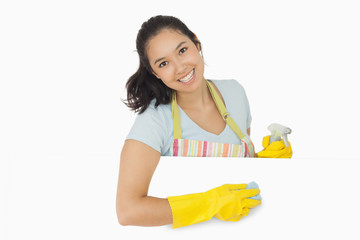 Happy woman wiping white surface