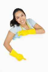 Happy cleaning lady pointing to white surface
