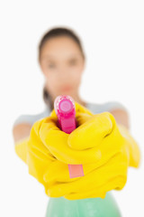 Confident woman pointing a spray bottle at the camera