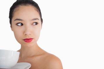 Woman holding a cup of coffee looking away