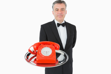 Waiter holding red phone
