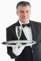 Smiling man serving champagne on tray