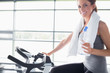 Woman holding a bottle and riding a exercise bike