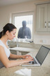 Woman using laptop with robber looking at her through window