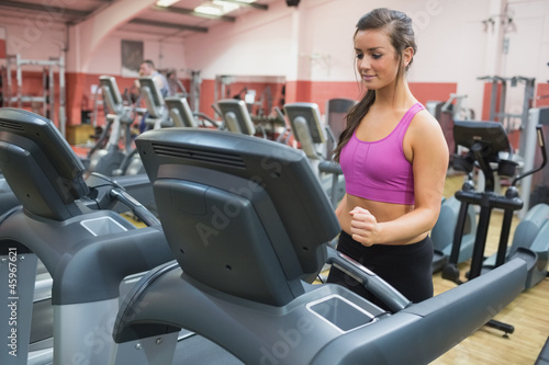 Woman running on a treadmill in a gym looking down