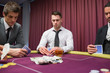 Men looking at their hands in high stakes poker game