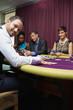 Smiling dealer at poker game