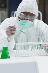 Chemist adding green liquid to test  tubes