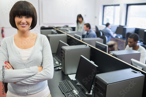 Teacher standing at front of computer class with arms crossed