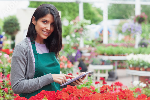 Smiling employee using tablet pc to check flowers