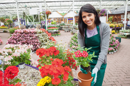 Cheerful woman planting a flower in a flower pot
