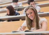 Woman sitting at the lecture hall while smiling