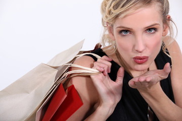 Woman with store bags blowing a kiss to camera
