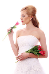 Young bride smelling red rose
