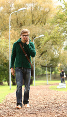 Young and handsome guy walking with cellphone in the autumn park