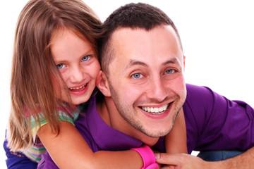 Cute little girl enjoying piggyback ride with her father over a