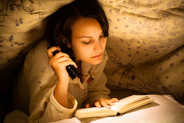 Serious Woman Reading a Book with Flashlight on Bed