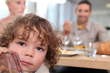 little boy sitting at table with parents in background
