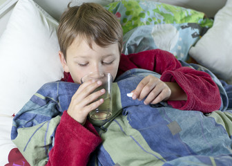 Young boy in bed taking his medicin