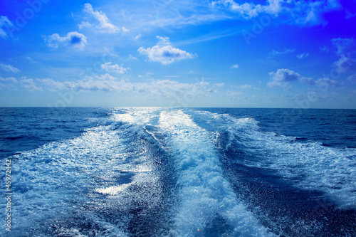 Boat wake prop wash foam in blue sky