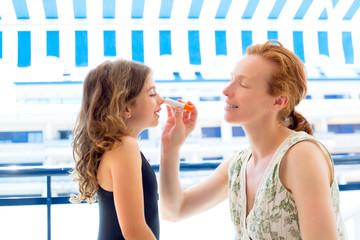 children girl with mother applying sunscreen