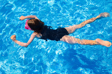 bikini kid girl swimming on blue tiles pool in summer