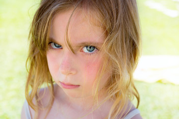 Angry blond children girl portrait looking camera