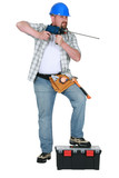Tradesman holding a drill with a long bit poster