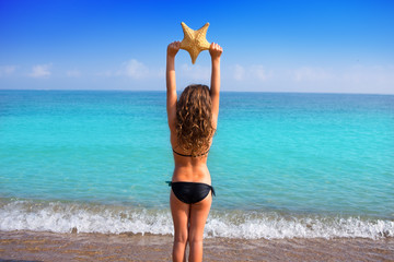 blue beach girl with bikini holding starfish rear view