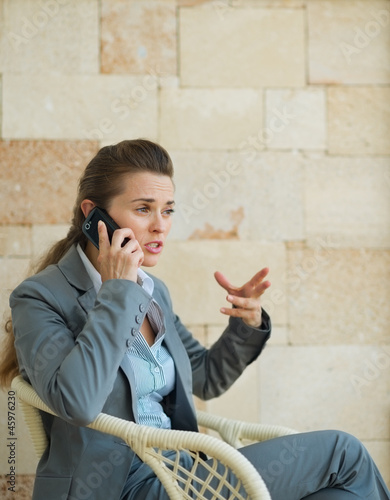Concerned business woman speaking mobile phone