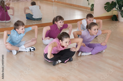 Group of children engaged in physical training indoors.