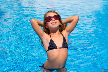 bikini kid girl with sunglasses in blue pool