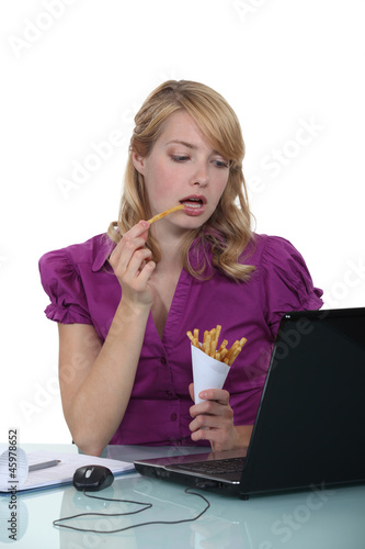 Woman eating French fries at desk