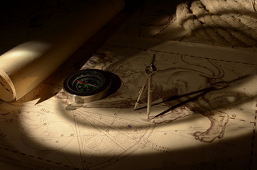 Old compass, calipers and rope on vintage map