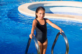 children girl on the blue pool stairs black swimsuit
