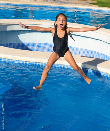 children girl jumping to the blue pool black swimsuit