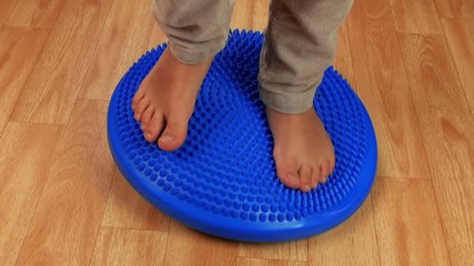 Children feet on the massage pillow