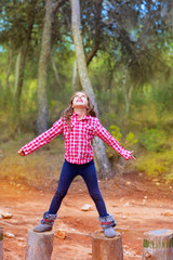 kid girl climbing tree trunks with open arms