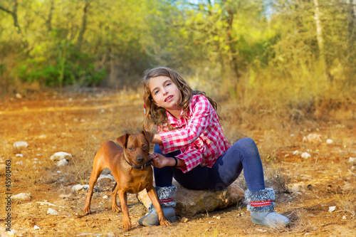 girl sitting in the pine forest holding little dog