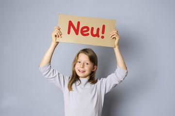 """Mädchen hält ein Schild mit """"Neu""""-Schriftzug"""