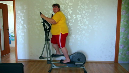 overweight woman exercising on trainer ellipsoid