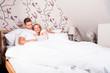 junges Paar liest im Bett per Tablet Computer